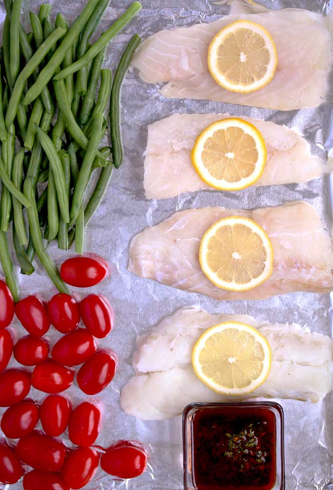 Raw fish and vegetables on a sheet pan and a bowl of chermoula sauce