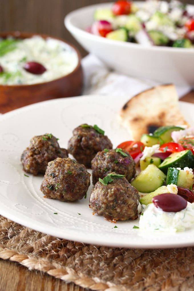 These Baked Greek Meatballs are seasoned with grated onion, garlic, oregano, fresh parsley and mint. Perfectly juicy and golden brown, they are great served as an appetizer or as part of dinner!