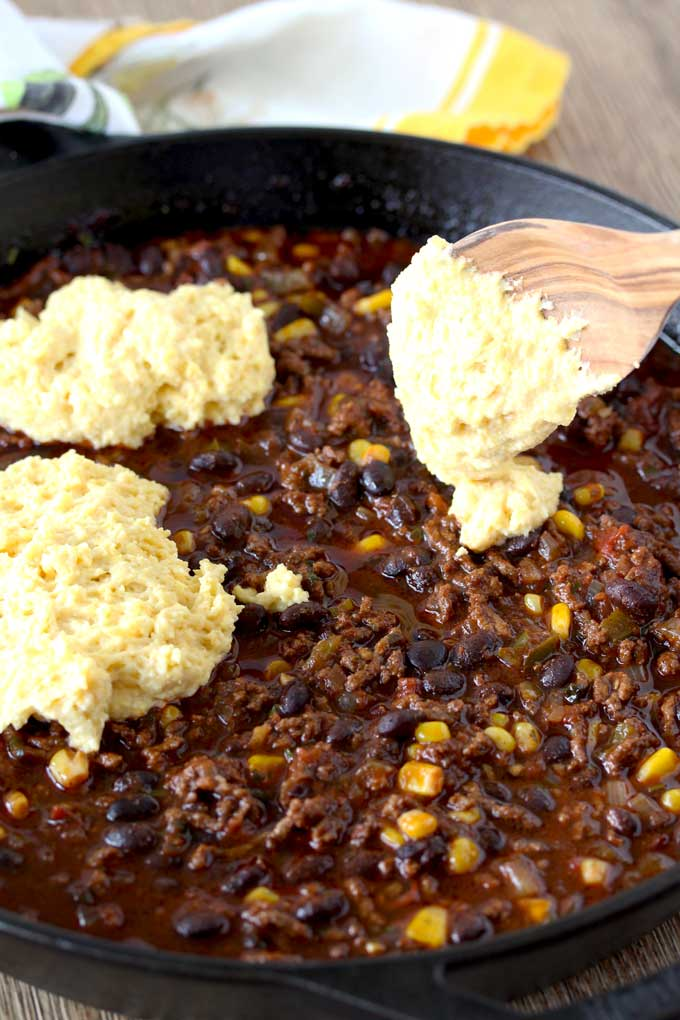 Raw Cornbread is dolloped over a mixture of ground beef chili with beans and corn, using a wooden spoon.