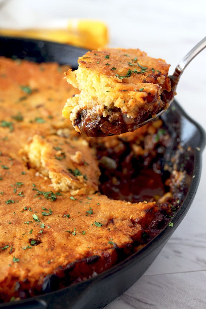 View of a serving spoon scooping a portion of cornbread tamale pie off a cast iron skillet