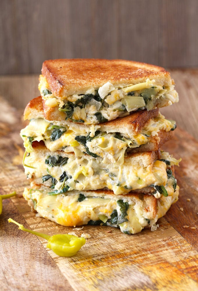 Buttery and toasty bread with an incredibly gooey and delicious filling. This easy Spinach and Artichoke Dip Cheese Melt is everything a grilled cheese sandwich should be and then some!! The addition of peperoncini adds brightness and zing to this delicious sandwich!