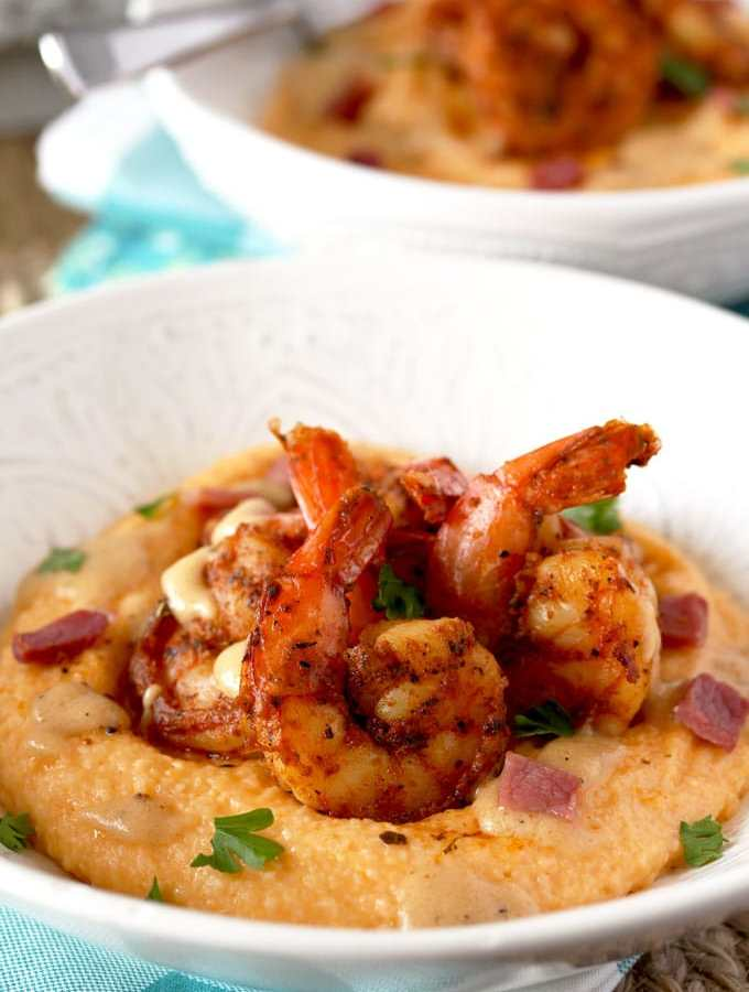These Shrimp and Grits have the perfect balance of flavors. Bold and Spiced Cajun Shrimp on a bed of creamy and cheesy grits. Finished with a drizzle of the most delicious, rich and buttery sauce!