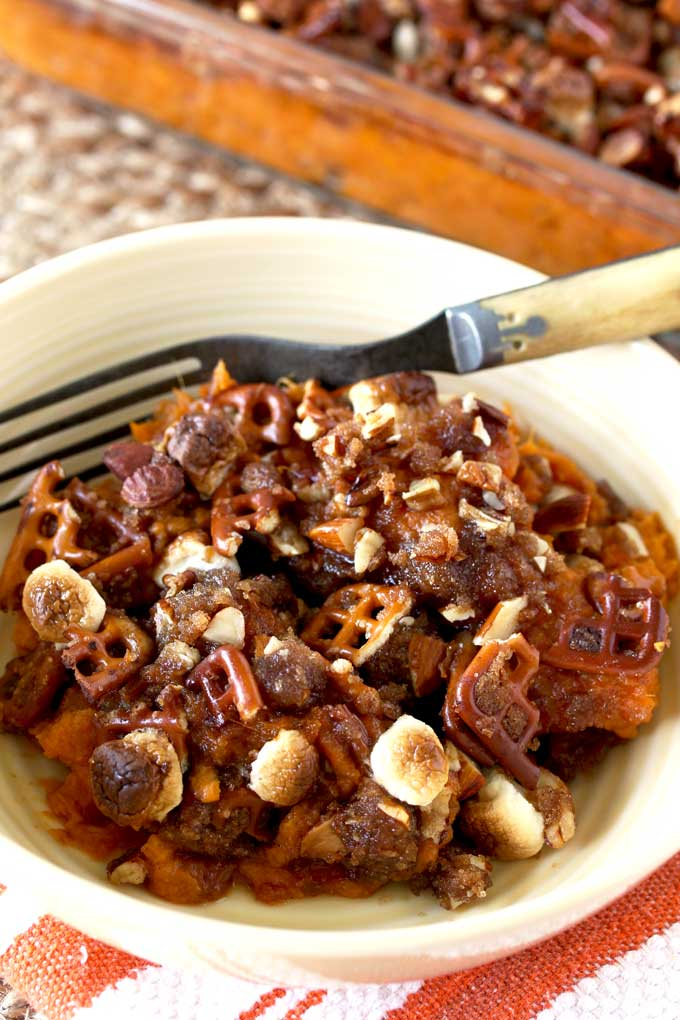 Close up view of a serving of sweet potato casserole in a small bowl. You can see a fork and also the topping which is made from pretzel pieces, browned roasted marshmallows and almonds.
