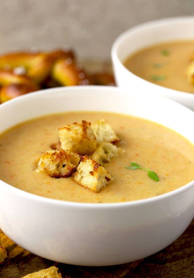 A close-up view of creamy Cheddar Ale Soup topped with crispy croutons served on a white soup bowl. Garnished with 2 thyme leaves