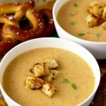 Close up view of two white bowls of Cheddar Ale Soup topped with croutons and lightly garnished with thyme leaves. On the side there are two salted pretzels on a wooden board,