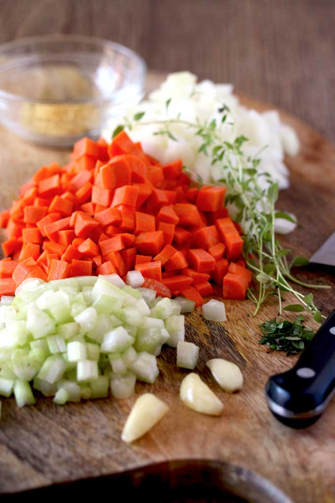 Diced celery, diced carrots, diced onions, whole garlic cloves and fresh thyme on a cutting board next to a chef's knife.
