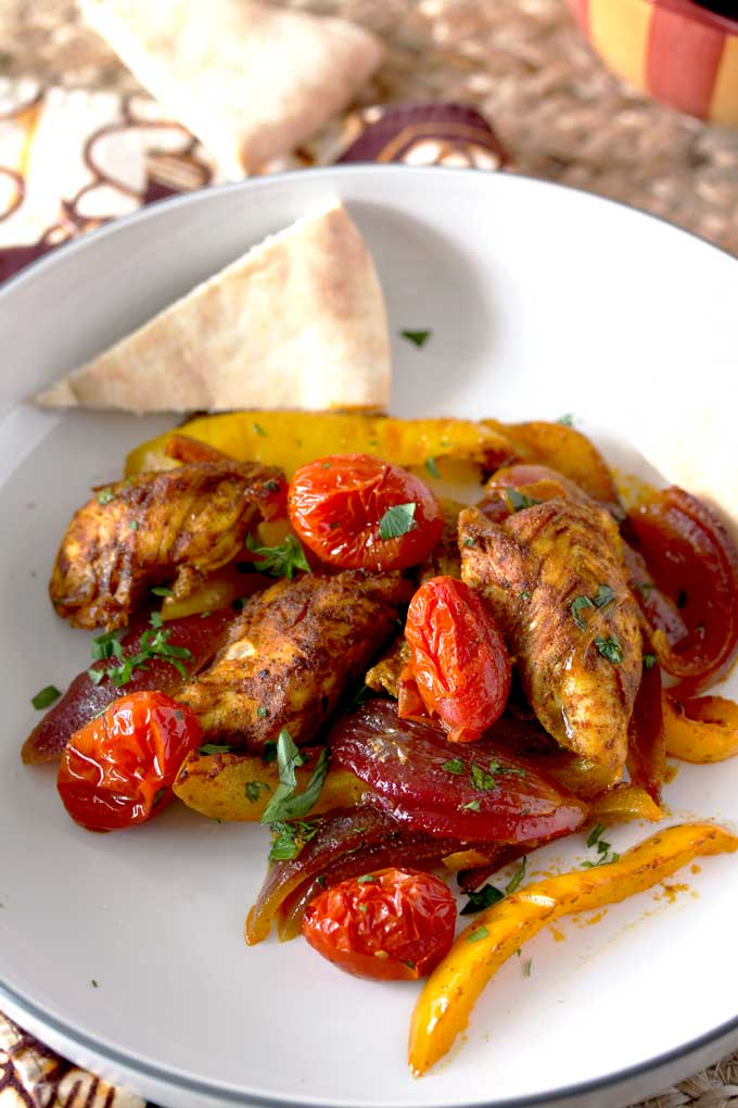 Close-up view of chicken tenders mixed with sliced yellow bell peppers, sliced red onions and cherry tomatoes served on a white plate and garnished with chopped parsley. A pita bread triangle set on one side of the plate.