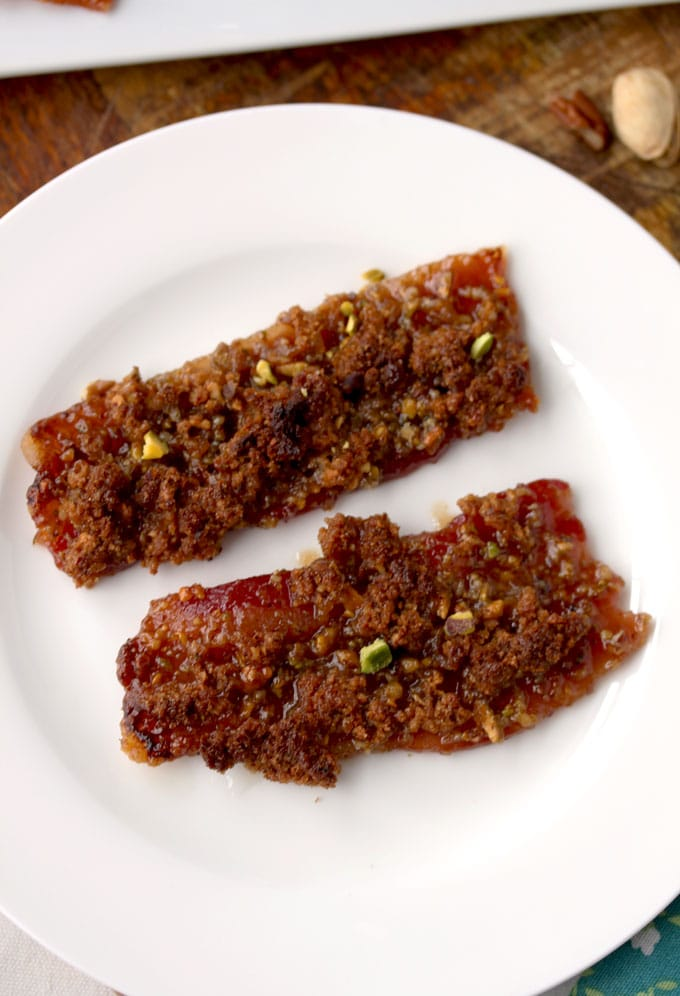 A closed up view of two strips of crispy and crunchy Nutty Maple Brown Sugar Bacon Appetizer on a white plate.