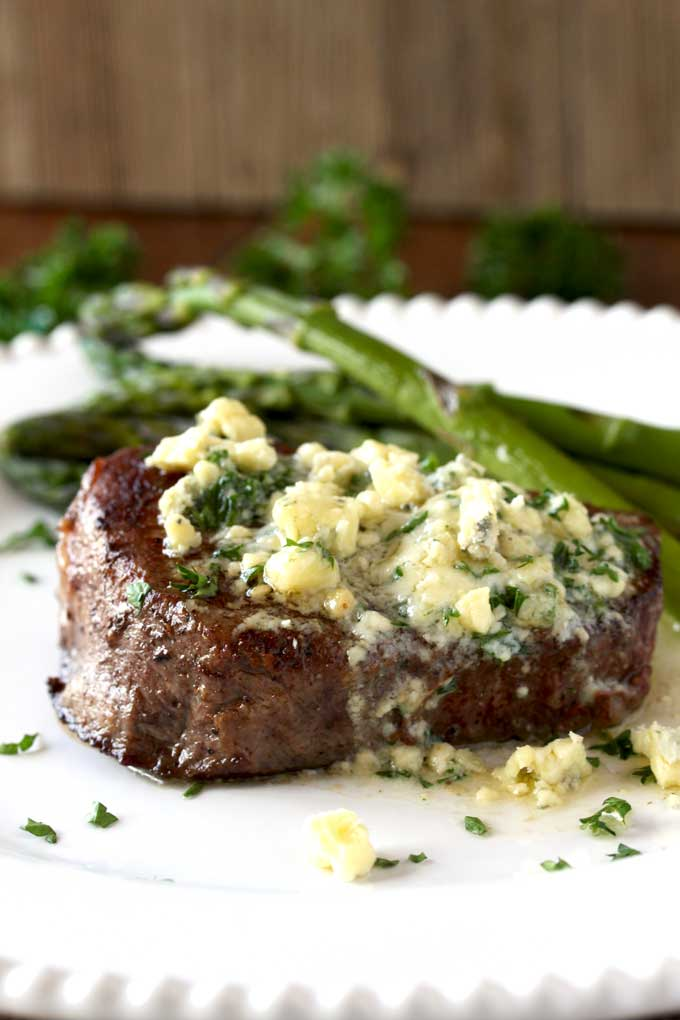 Closed up view of a pan seared filet mignon topped with blue cheese butter. The butter is melting and you can see some blue cheese crumbles and chopped parsley sitting on a white plate. Next to the filet mignon, sauteed asparagus.