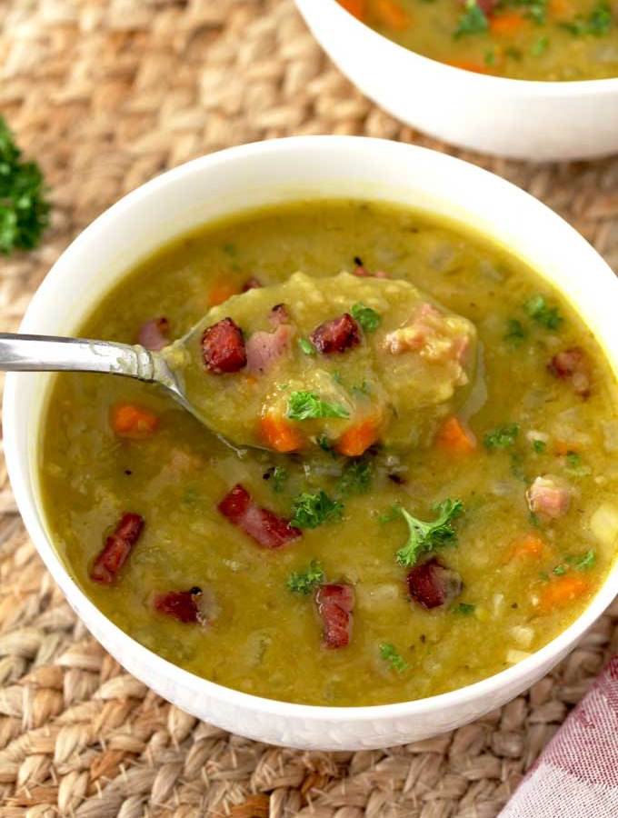 In this photo a spoon scooping out some split pea soup with ham from a white soup bowl.