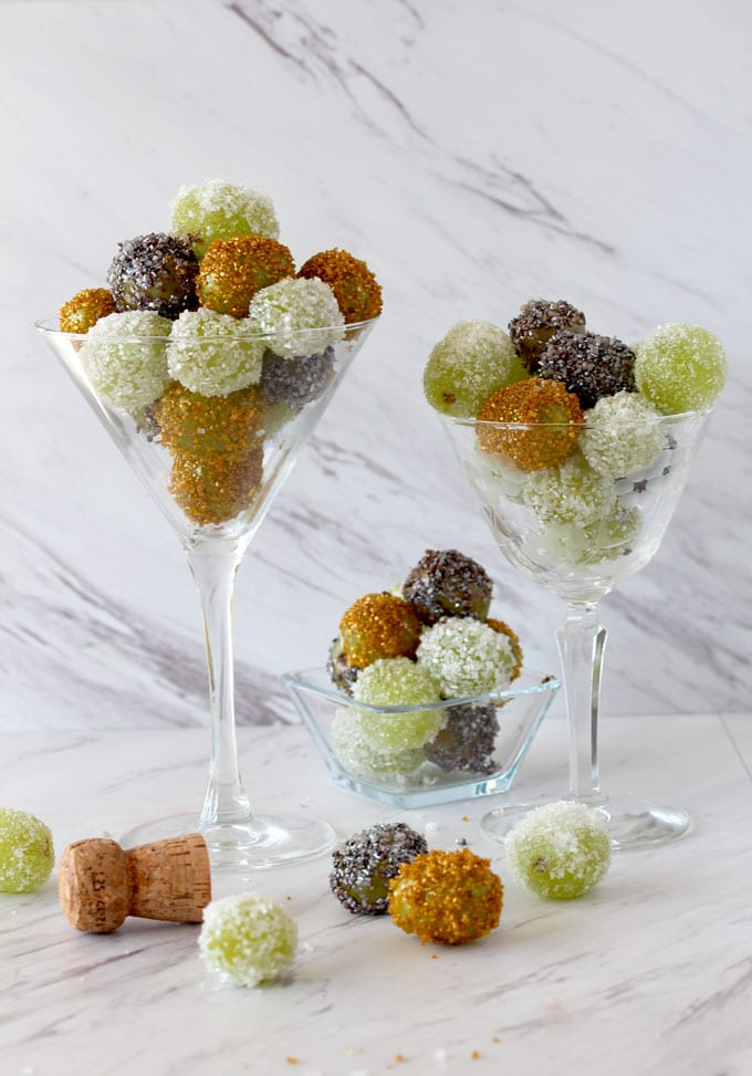 View of three crystal glasses filled with Prosecco Sugared Grapes covered in silver, gold and sparkling white sugars on a white marble surface.