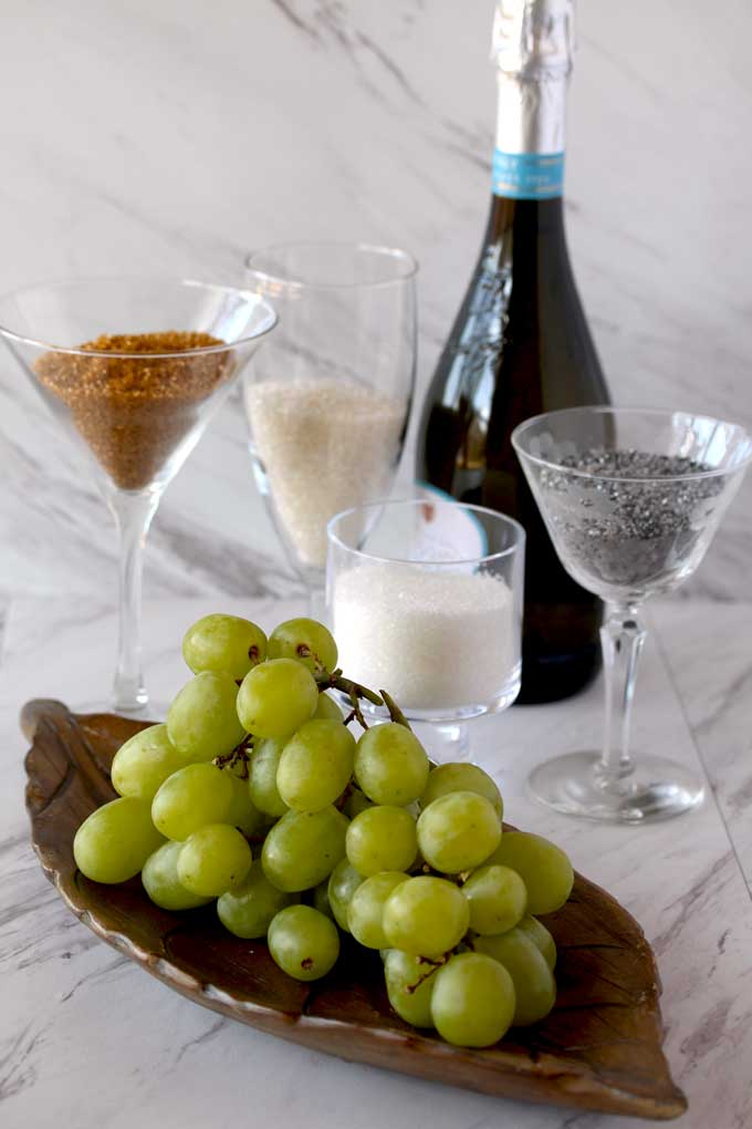 Ingredients for making Prosecco Sugared Grapes sitting on a white marble counter. A bunch of greenn grapes, sanding sugars and a bottle of Prosecco.
