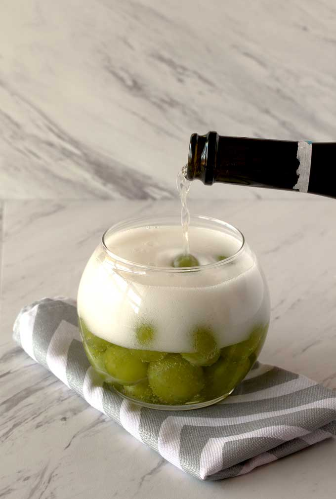 Bubbly Prosecco pouring into a bowl filled with green grapes