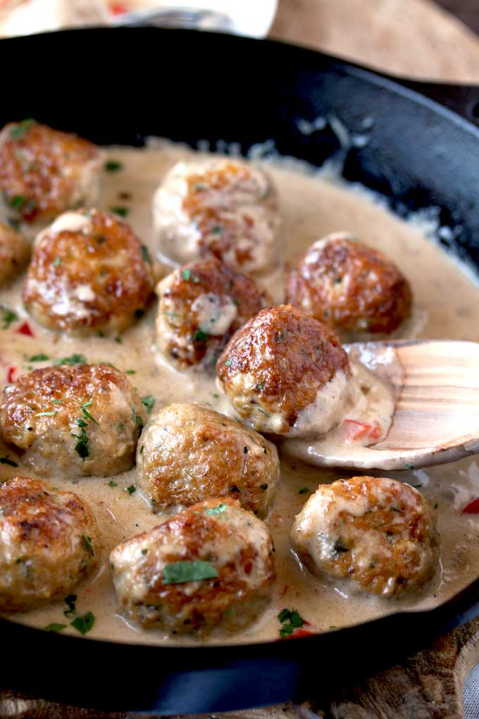 Close up view of a chicken meatball scooped up with a wooden spoon from a cast iron skillet