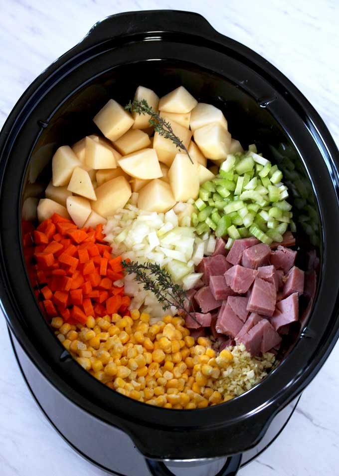 Pictured here is a slow cooker filled with cubed potatoes, ham, chopped onions, celery, carrots, corn, minced garlic and thyme sprigs.