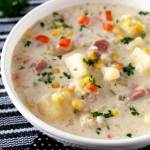 Pictures a big bowl of creamy slow cooker ham and potato soup with diced ham, potatoes, carrots and corn on a black and white table mat.