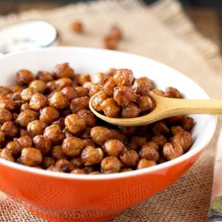 Pictured here is a small orange bowl filled with crispy oven roasted chickpeas. A small wooden spoon si scooping out some chickpeas from the bowl.
