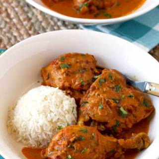 View of a white bowl filled with Chicken Masala and white rice.