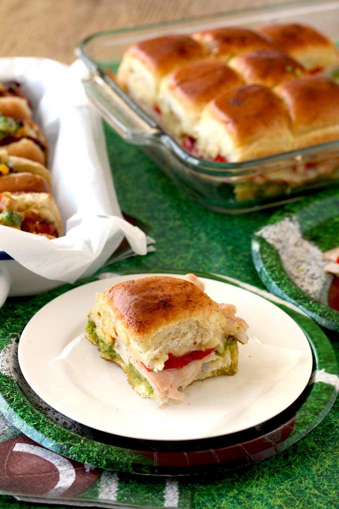 A Turkey Pesto Slider set on a table filled with other Game Day Foods