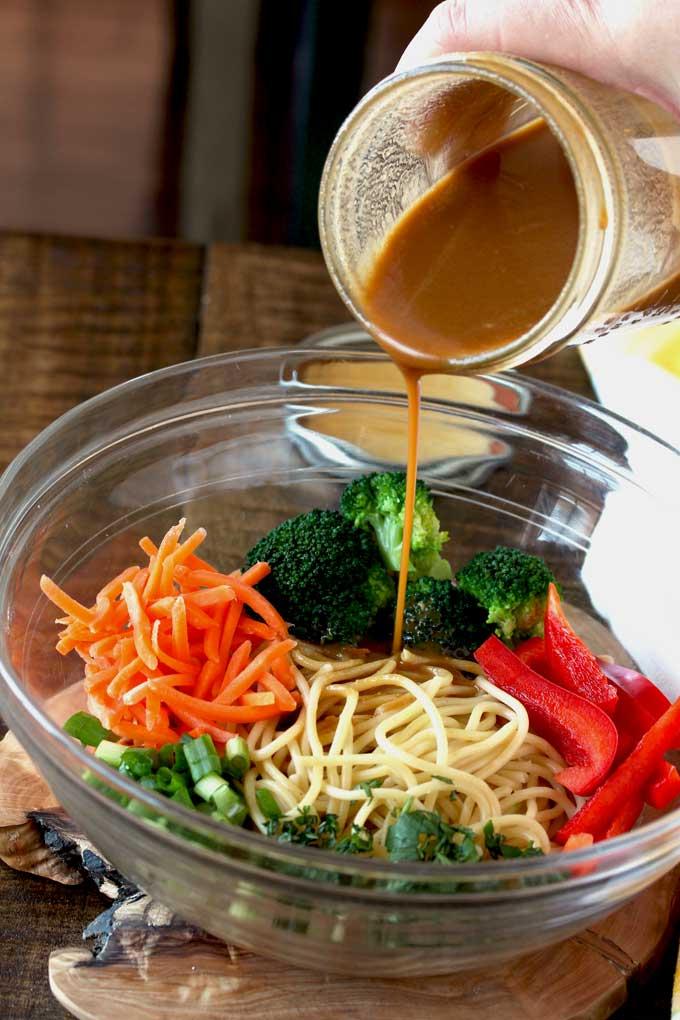 Peanut Sesame Dressing poured over noodles and vegetables.