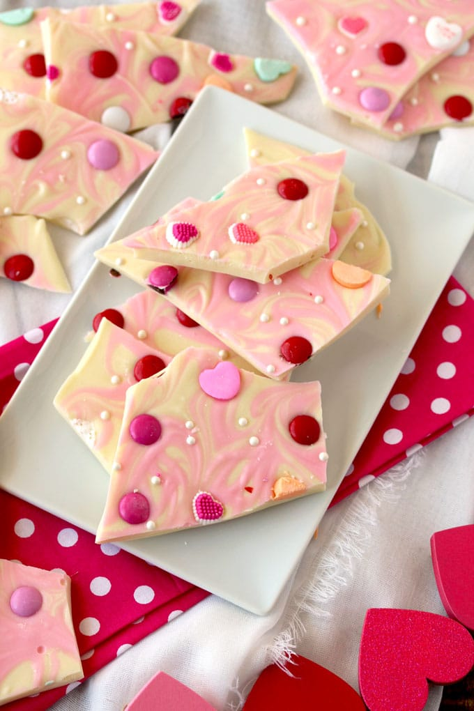 Pieces of white chocolate valantines bark on a rectangular white plate.