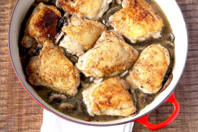 Golden brown chicken thighs cooking with mushrooms, white wine and stock