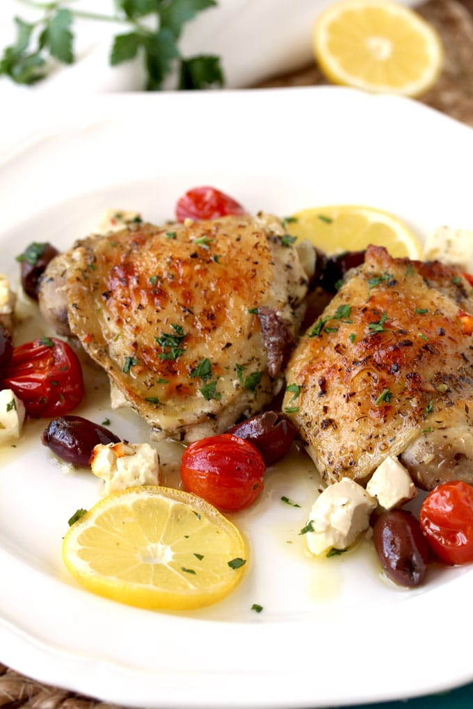 Greek Lemon Oven Roasted Chicken Thighs pieces served on a white plate. Garnished with lemon slices