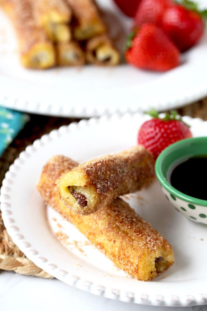 Two Nutella French Toast Roll-Ups on a small white plate next to a bowl of maple syrup