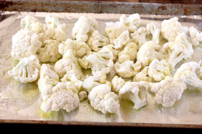 Raw cauliflower florets drizzled with olive oil on a baking sheet pan