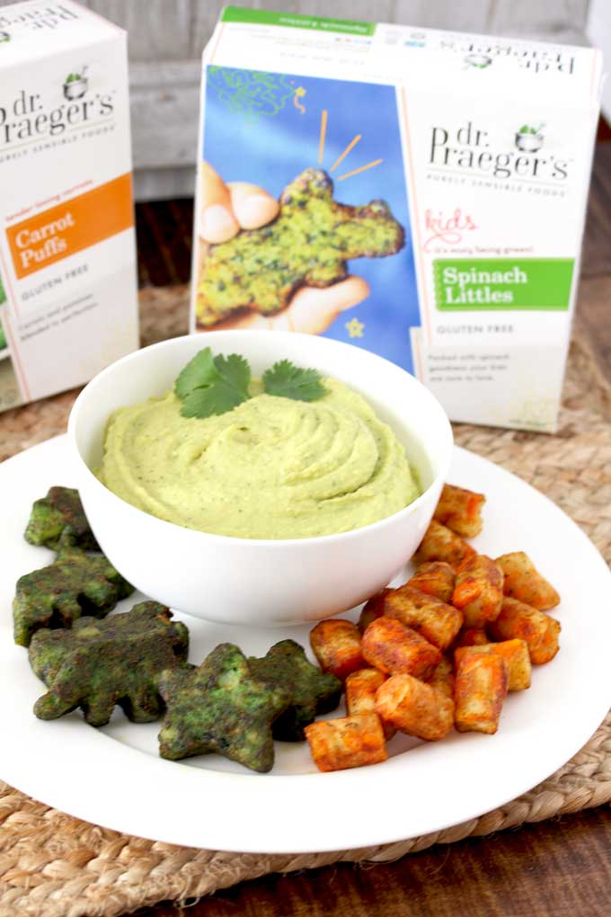 A white bowl with creamy avocado hummus and spinach littles and carrot puss as dippers.