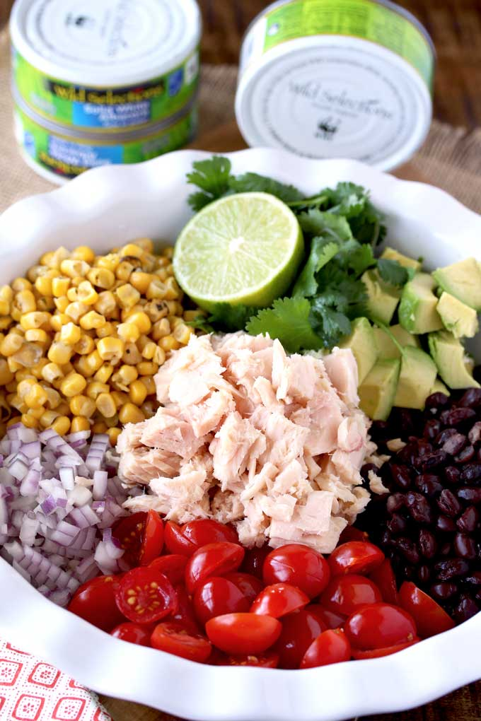 Pictured here a plate with the ingredients to make Mexican Tuna Salad. White albacore tuna, roasted corn, chopped red onions, tomatoes, black beans, avocado and cilantro.