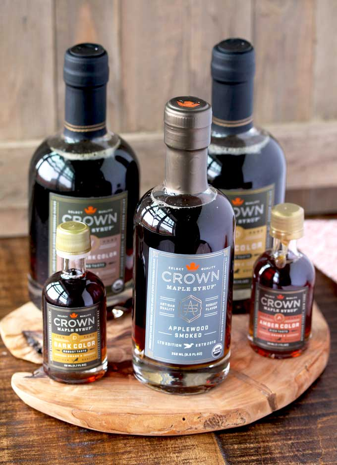 A collection of bottles of Crown Maple syrup on a wooden board
