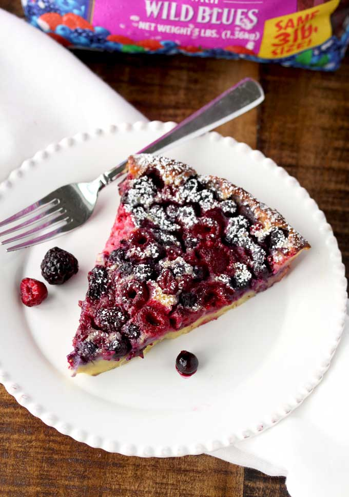 A big slice of mixed berry clafoutis on a white plate