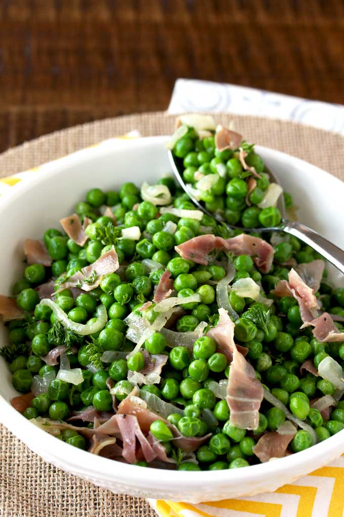 A white bowl filled with sauteed peas with prosciutto and shallots