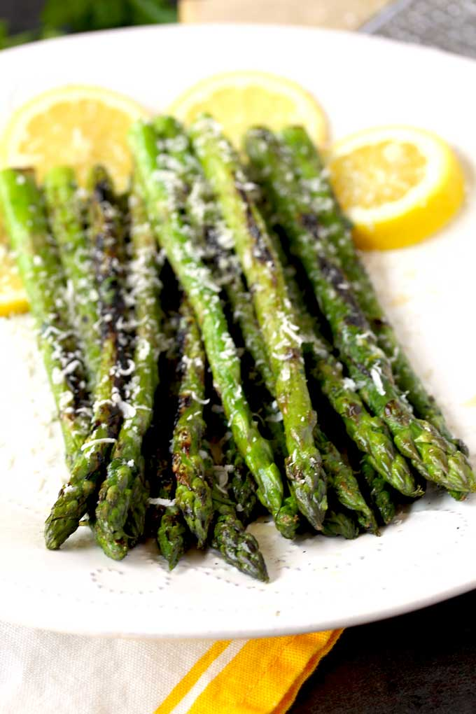 Closed up view of grilled asparagus on a white plate