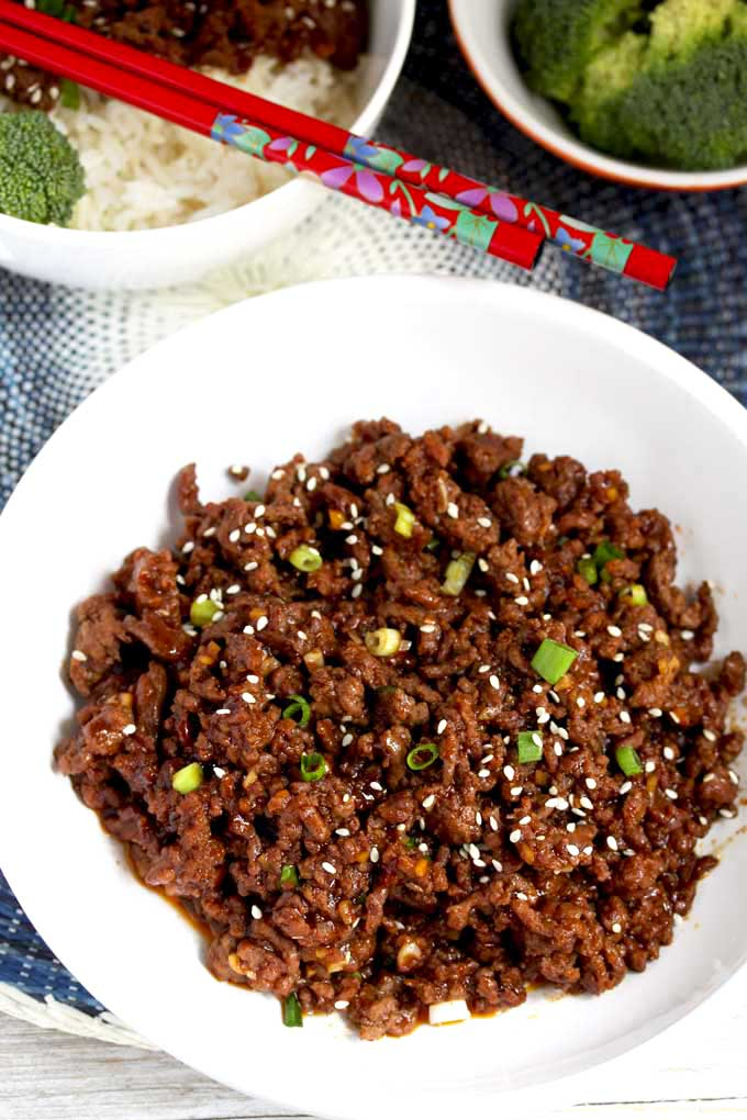 Korean Beef in a white bowl garnished with scallions and sesame seeds.