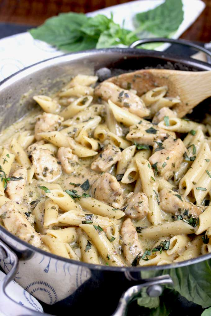 Chicken Pesto Pasta in a pan scooped out by a wooden spoon
