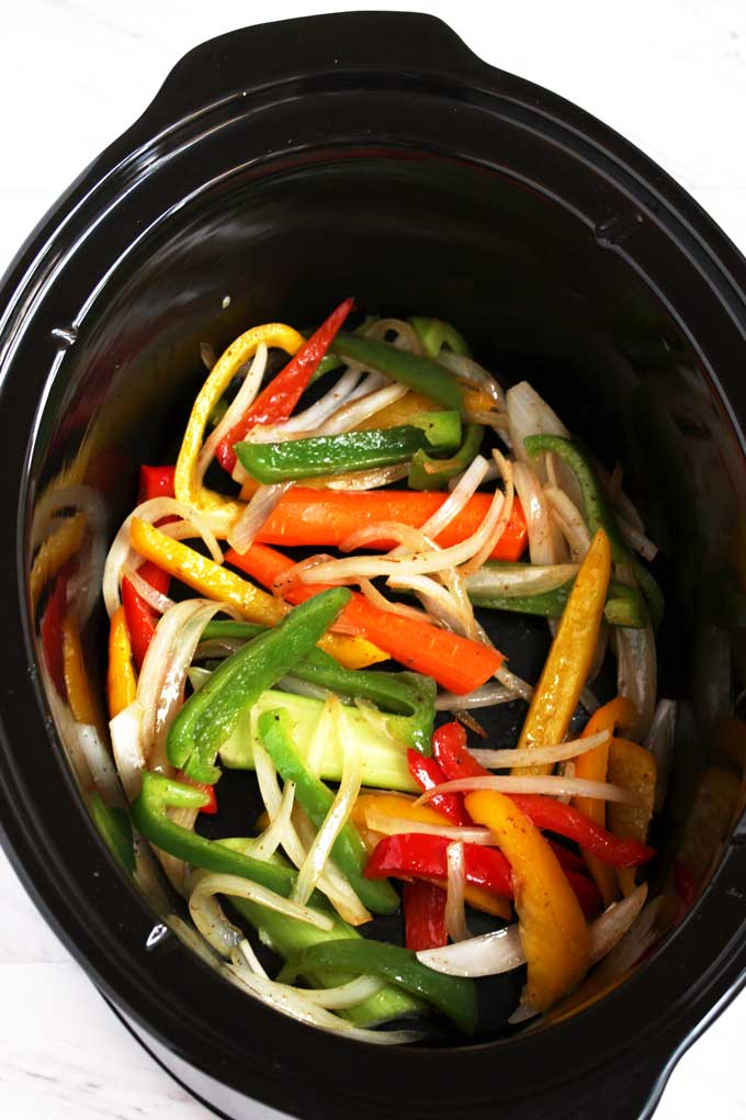 Sauteed onions and peppers, carrots and celery at the bottom of a slow cooker.
