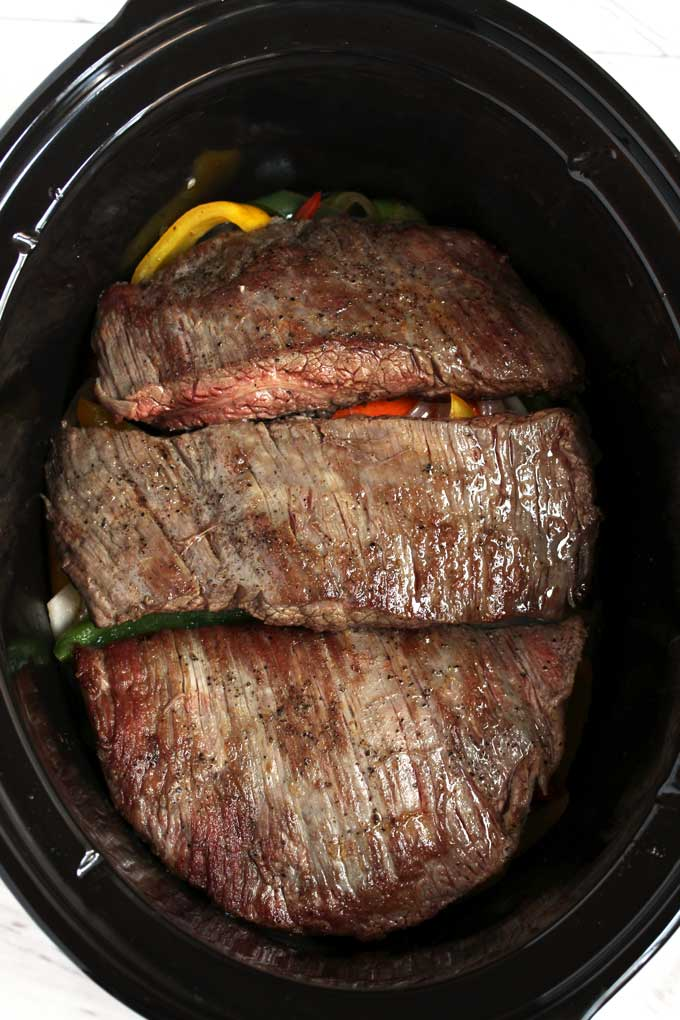 Seared flank steak on top of sauteed onions and peppers inside a slow cooker.