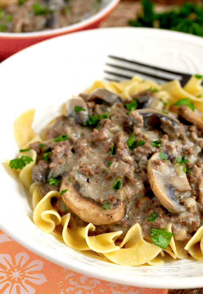 Ground Beef Stroganoff over egg noodles in a white bowl