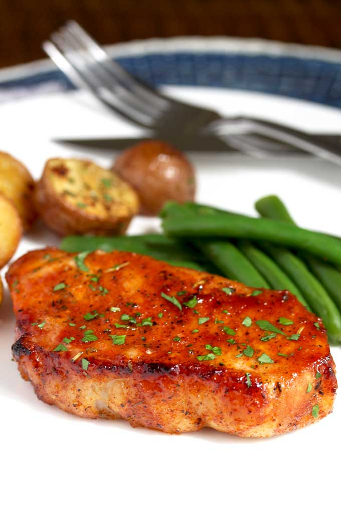 Close up of an oven baked pork chop on a white plate with roasted potatoes and green beans.