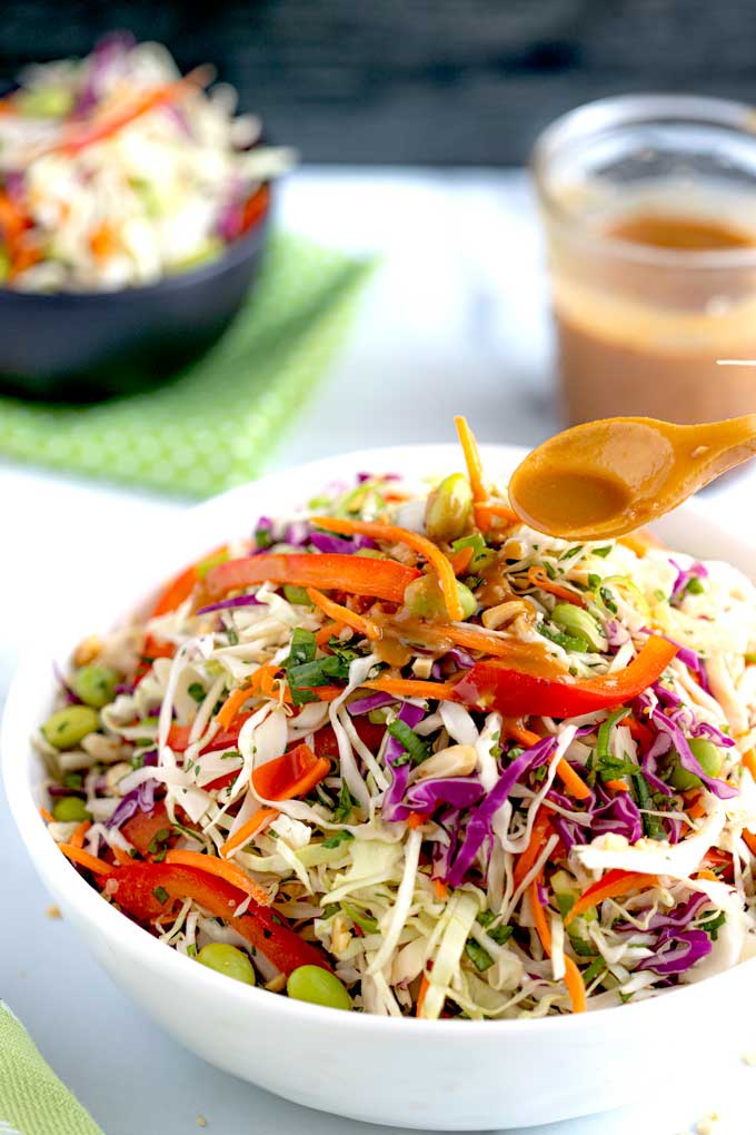 A bowl coleslaw getting drizzled with Peanut dressing.