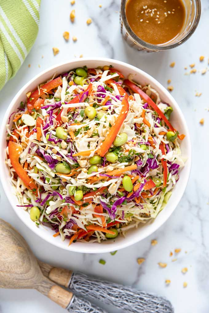 Top view of a bowl filled with Asian Coleslaw next to a container filled with Ginger Sesame Peanut Dressing.