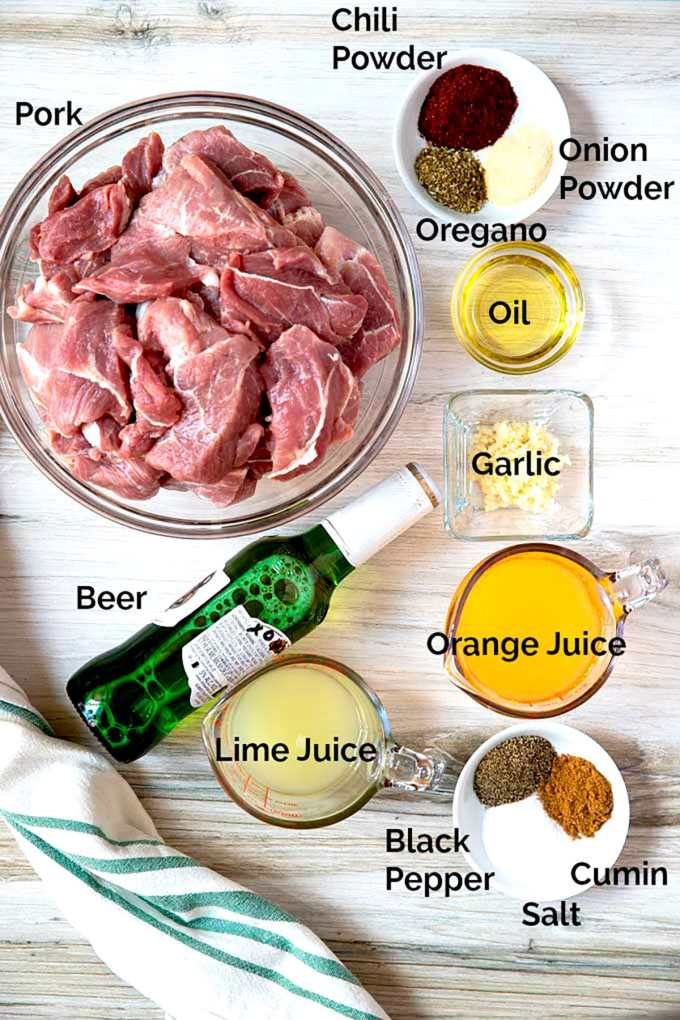 Picture here all the ingredients to make this pork recipe on a white surface.
