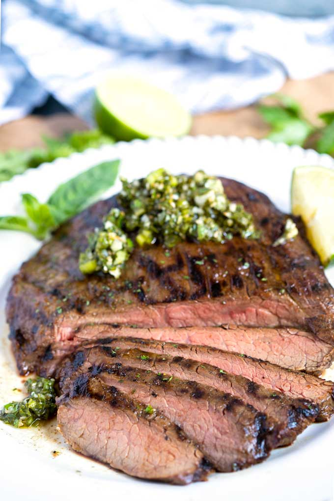 Sliced grilled flank steak topped with herb chimichurri on a white platter.