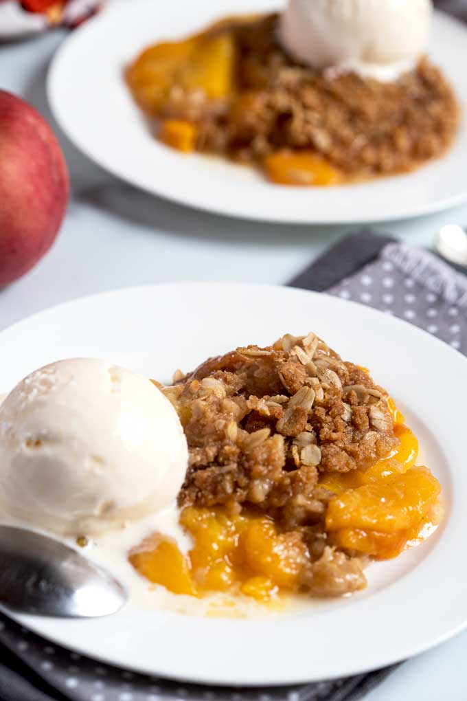 Baked peach crisp topped with vanilla ice cream on a white plate