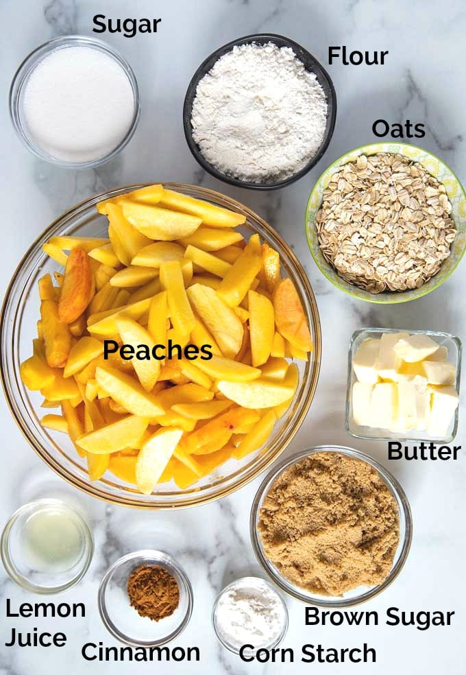 Ingredients to make peach crisp on a marble surface.