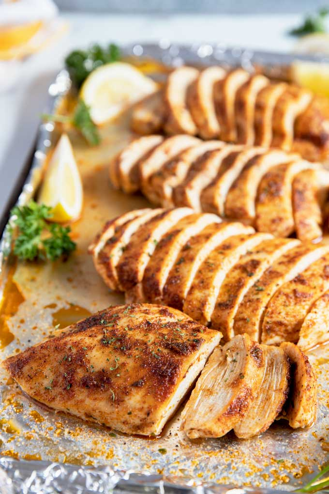 Sliced baked chicken breasts on a baking sheet