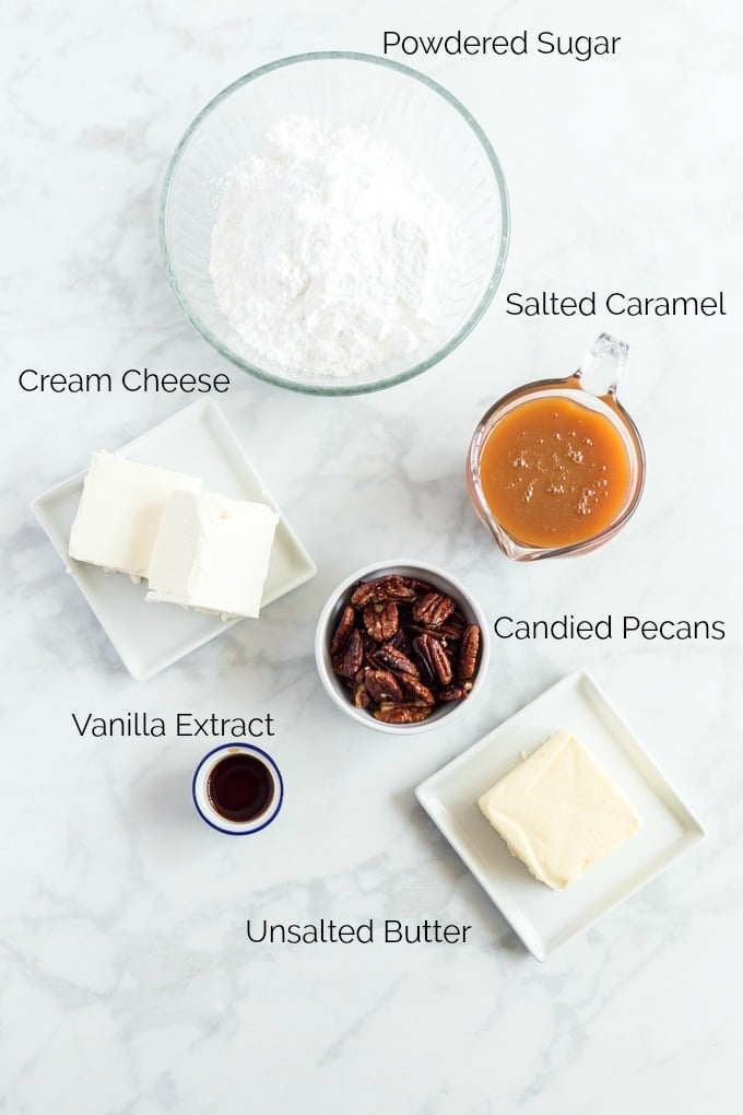 Salted Caramel Cream Cheese Frosting Ingredients and topping on a white surface