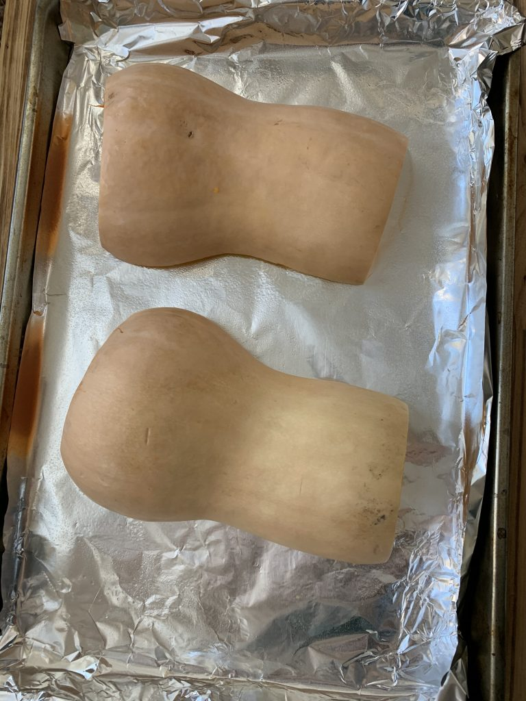 butternut squash on baking sheet ready to be cooked in oven